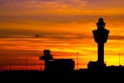 an airport terminal and control tower at sunset