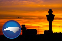 north-carolina map icon and an airport terminal and control tower at sunset