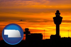 nebraska map icon and an airport terminal and control tower at sunset