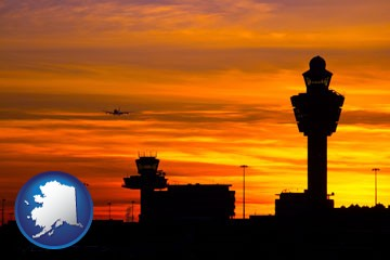 an airport terminal and control tower at sunset - with Alaska icon