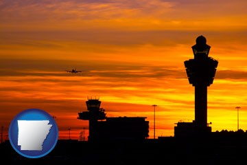 an airport terminal and control tower at sunset - with Arkansas icon