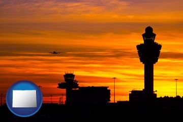 an airport terminal and control tower at sunset - with Colorado icon