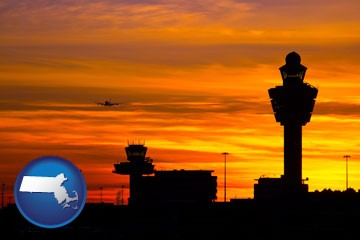 an airport terminal and control tower at sunset - with Massachusetts icon