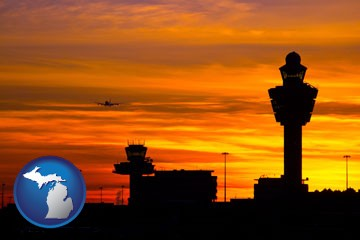 an airport terminal and control tower at sunset - with Michigan icon