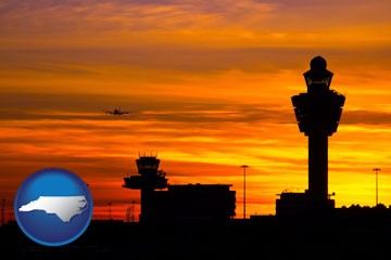 an airport terminal and control tower at sunset - with North Carolina icon