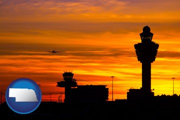 an airport terminal and control tower at sunset - with Nebraska icon