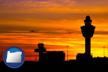 an airport terminal and control tower at sunset - with Oregon icon