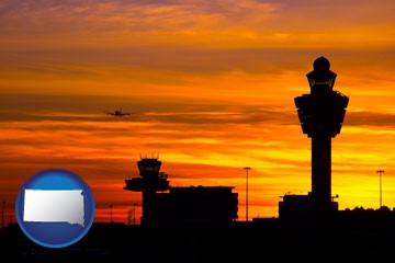 an airport terminal and control tower at sunset - with South Dakota icon